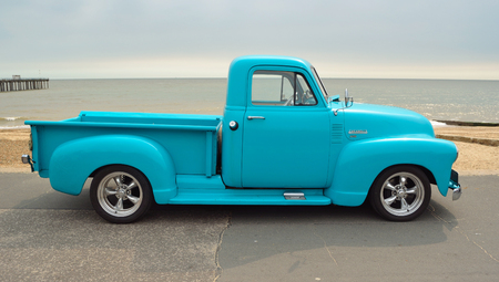 Classic Light Blue  Chevrolet 3100 pickup truck on seafront promenade with sea in background