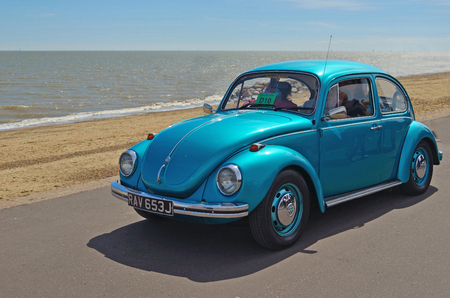 Classic Blue  Volkswagen Beatle being driven along Felixstowe seafront promenade.