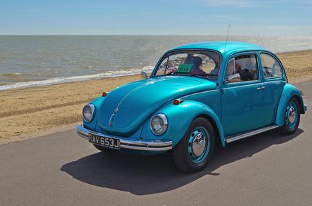 Classic Blue Volkswagen Beatle samen Felixstowe boulevard wordt gereden.