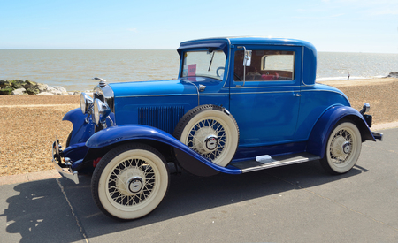 felixstowe: FELIXSTOWE, SUFFOLK, ENGLAND - MAY 01, 2016: Vintage  Blue Motorcar with white wall tyres parked on seafront promenade.