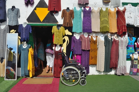 shopfront: TEGUISE, LANZAROTE, SPAIN - NOVEMBER 20, 2016: Shopfront with colorful garments hanging on wall with Wheelchair left outside and mirror. Editorial