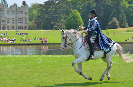 stately home: SAFFRON WALDEN, ESSEX, ENGLAND - JUNE 05, 2016: Man in Elizabethan costume with sword on a horse galloping  in front of stately home.