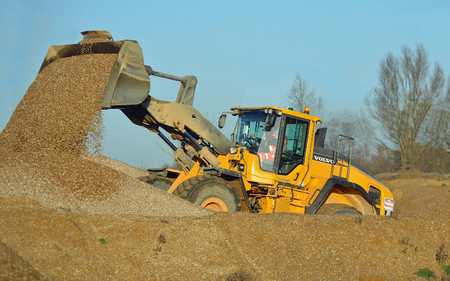 buildingsite: LITTLE PAXTON, CAMBRIDGESHIRE, ENGLAND -  JANUARY 05, 2017: JCB working in gravel yard.