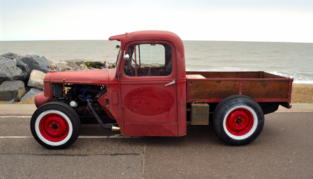 felixstowe: FELIXSTOWE, SUFFOLK, ENGLAND - AUGUST 27, 2016: Classic Hot Rod  pickup truck on seafront promenade with sea in background Editorial