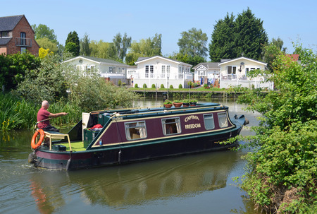 OFFORD CLUNY, CAMBRIDGESHIRE, ENGLAND - JUNE 09, 2016: Traditional Narrow boat on the river Ouse with riverside lodges at Buckden Marina Cambridgeshire.