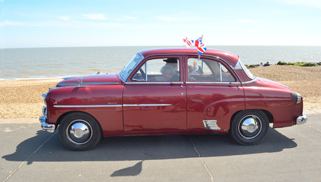 FELIXSTOWE, SUFFOLK, ENGLAND - MAY 01, 2016: Classic Red Vauxhall Velox Motor  being driven  on seafront promenade. Editorial