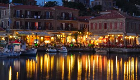 MOLYVOS, LESVOS, GREECE - JUNE 12, 2014: Holiday makers dining in harbor side restaurants Molyvos Greece Editorial