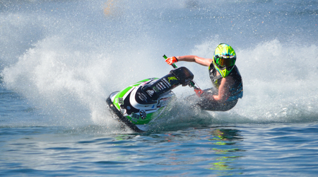 WYBOSTON, BEDFORDSHIRE, ENGLAND -  APRIL 09, 2017: Jet Ski competitor cornering at speed creating at lot of spray. 에디토리얼