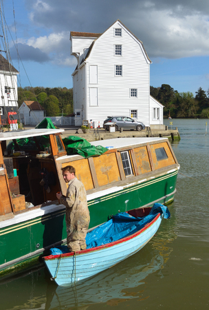 WOODBRIDGE, SUFFOLK, ENGLAND - APRIL 17, 2017: Man doing boat repairs at Woodbridge Quay with tide mill in the background.