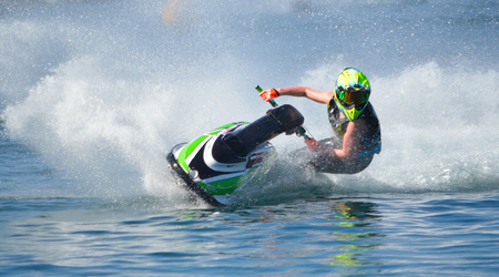 Jet Ski competitor cornering at speed creating at lot of spray.