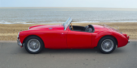 FELIXSTOWE, SUFFOLK, ENGLAND -  MAY 07, 2017: Classic  Red  MGA  Car  parked on seafront promenade with sea in background. Editorial