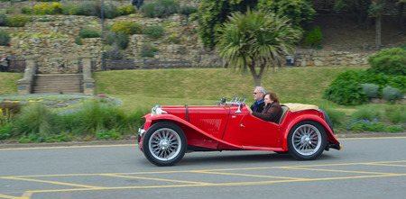 FELIXSTOWE, SUFFOLK, ENGLAND -  MAY 07, 2017: Classic Red  MG Sports car  being driven along road.