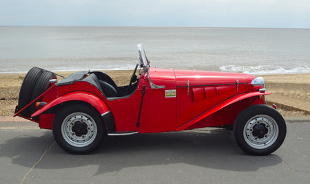 FELIXSTOWE, SUFFOLK, ENGLAND -  MAY 07, 2017: Classic Red Delon Sports - Trials Motor Car Parked on Seafront Promenade.