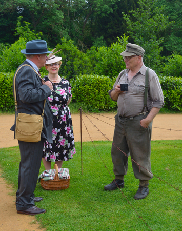 SILSOE, BEDFORDSHIRE, ENGLAND - MAY 28, 2017:  Two Men and a Woman Dressed in  in Second World War Clothes and Uniform.