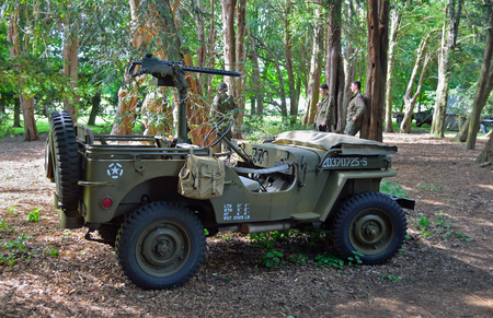 SILSOE, BEDFORDSHIRE, ENGLAND - MAY 28, 2017:  Second World War  Jeep with machine Gun parked in woods with men dressed in uniforms in background. Editorial
