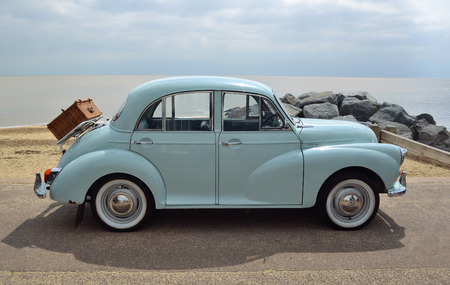 FELIXSTOWE, SUFFOLK, ENGLAND -  MAY 07, 2017: Classic Light Blue Morris Minor with picnic basket parked on seafront promenade. Editorial