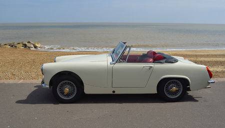 FELIXSTOWE, SUFFOLK, ENGLAND -  MAY 07, 2017: Classic  White - Cream  MG Midget Car  parked on seafront promenade with sea in background.