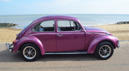 FELIXSTOWE, SUFFOLK, ENGLAND -  MAY 07, 2017: Classic Purple  Volkswagen Beetle Motor Car Parked on Seafront Promenade.