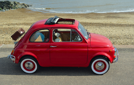 FELIXSTOWE, SUFFOLK, ENGLAND -  MAY 07, 2017: Classic Red Fiat 500  motor car with picnic basket parked on seafront promenade. Редакционное