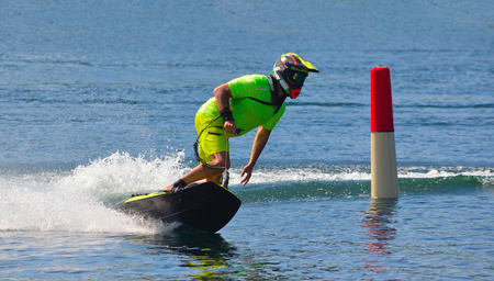Male Motosurf Competitor Taking corner at speed creating a lot of spray. Banque d'images