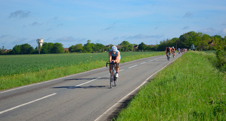 GRAFHAM, CAMBRIDGESHIRE, ENGLAND - MAY 21, 2017:  Triathletes on road cycling stage of triathlon.