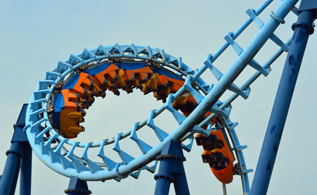 CORTON, SUFFOLK, ENGLAND - AUGUST 23, 2017: Roller coaster  ride filled  with thrill seekers doing corkscrew.