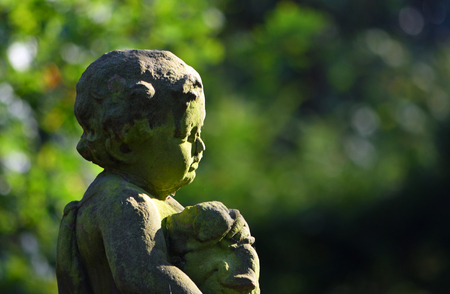 Silsoe, Bedfordshire, England - October 27, 2017: Detail of statue of small boy with puppy,