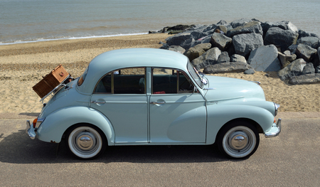 FELIXSTOWE, SUFFOLK, ENGLAND -  MAY 07, 2017: Classic Light Blue Morris Minor with picnic basket parked on seafront promenade. Редакционное
