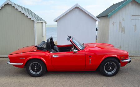 FELIXSTOWE, SUFFOLK, INGHILTERRA - 7 MAGGIO 2017: Automobile rossa classica di Triumph Spitfire parcheggiata sulla passeggiata del lungomare parcheggiata davanti alle capanne della spiaggia. Editoriali