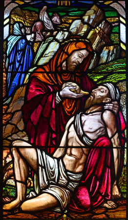 ROXTON, BEDFORDSHIRE, ENGLAND - JUNE 30, 2018: Stained Glass Window Depicting the Good Samaritan in Roxton Chapel.