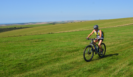 ALCISTON, EAST SUSSEX, ENGLAND - SEPTEMBER 01, 2018 : Female Mountain biker riding the South Downs near Bo Peep Hill East Sussex. Editorial