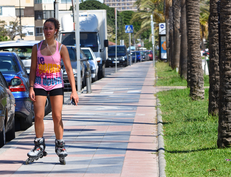 TORREMOLINOS, ANDALUCIA,  SPAIN -  SEPTEMBER 24, 2018: Attractive  Young Woman Roller Skating along Sidewalk.
