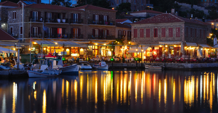 MOLYVOS, LESVOS, GREECE - JUNE 12, 2014: Holiday makers dining in harbor side restaurants Molyvos Greece Editorial