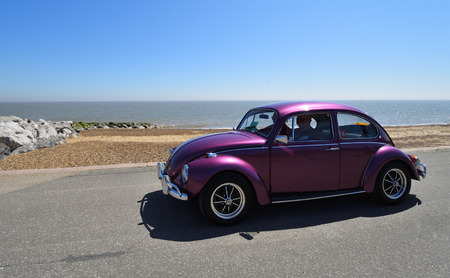 FELIXSTOWE, SUFFOLK, ENGLAND - MAY 06, 2018:  Classic Purple  VW Beetle Motor Car being driven along Seafront  Promenade.