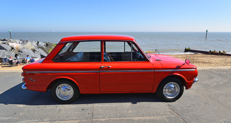 FELIXSTOWE, SUFFOLK, ENGLAND -  MAY 07, 2017: Classic Red Hillman Imp Motor Car parked on seafront promenade.