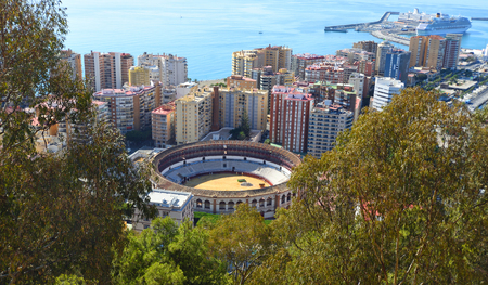 Malaga City Bull Ring Plaza de Toros      or La Malagueta  viewed from above with tower blocks harbour and the Ocean in background. Banco de Imagens