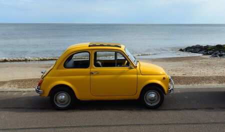 FELIXSTOWE, SUFFOLK, ENGLAND - MAY 06, 2018: Classic Yellow Fiat 500 parked on seafront promenade.