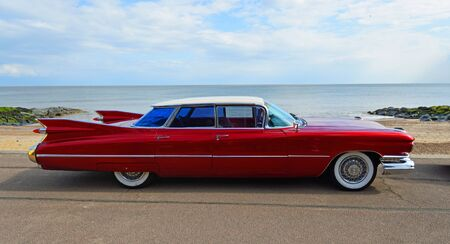 FELIXSTOWE, SUFFOLK, ENGLAND - MAY 05, 2019: Classic Red 1950's 4 door Cadillac  motor car parked on seafront promenade.