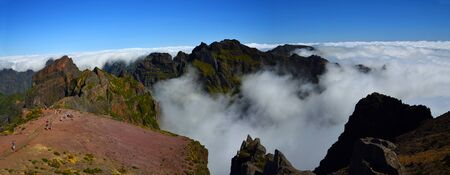 Panorama of Pico do Areeiro Madeira peaks among clouds with blue sky above.