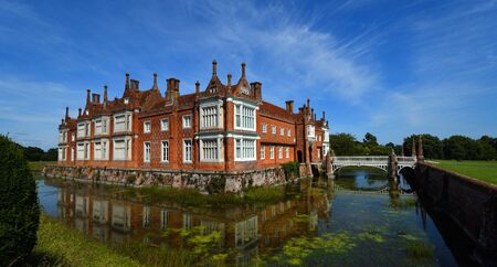HELMINGHAM, SUFFOLK, ENGLAND - AUGUST 22, 2019:  Helminngham Hall with moat bridge and reflections. Editorial