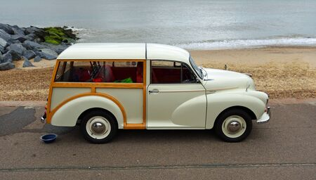FELIXSTOWE, SUFFOLK, ENGLAND - MAY 05, 2019: Classic Cream Coloured Morris 1000 Traveller parked on seafront promenade beach and sea in the background.