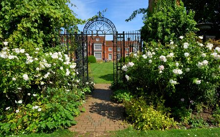 Helminngham Hall Gardens with roses and iron gate.