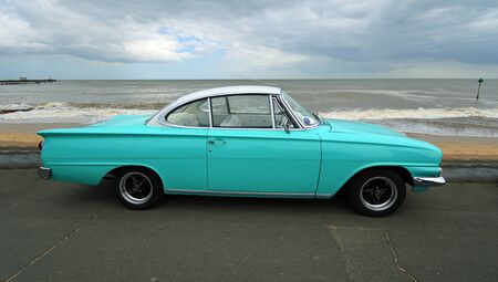 FELIXSTOWE, SUFFOLK, ENGLAND - MAY 05, 2019: Rare Classic  Light Blue and White Ford  Consul Capri Motor Car parked on seafront promenade with beach and sea in background.