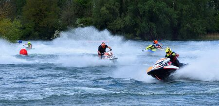 Jet Ski race competitors cornering at speed creating at lot of spray.