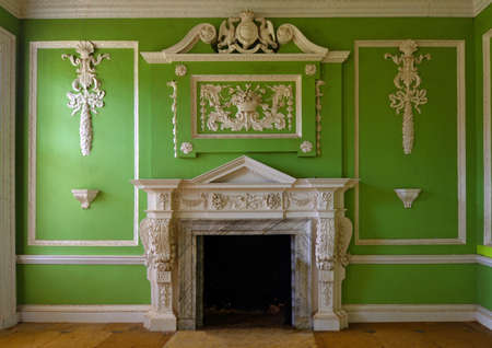 SILSOE, BEDFORDSHIRE, ENGLAND -  SEPTEMBER 04, 2020: Ornate marble chimneypiece and decorative plaster panels, dado and cornices