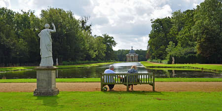 SILSOE, BEDFORDSHIRE, ENGLAND -  SEPTEMBER 04, 2020: Couple sitting on bench overlooking the Thomas Archer pavillion and Long Canal at Wreat Park.