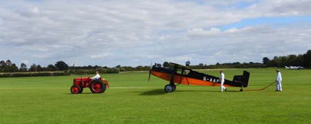 ICKWELL, BEDFORDSHIRE, ENGLAND - SEPTEMBER 06, 2020: Vintage  1931 Desoutter 1 High Wing aircraft  being towed by vintage tractor.