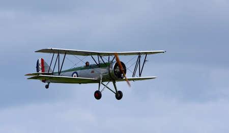 ICKWELL, BEDFORDSHIRE, ENGLAND - SEPTEMBER 06, 2020: Vintage Avro 621 Tutor Aircraft in flight dark cloud background. Editorial
