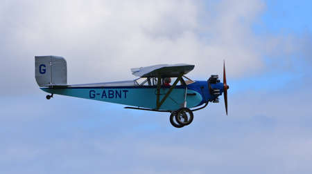 ICKWELL, BEDFORDSHIRE, ENGLAND - SEPTEMBER 06, 2020: Vintage 1931 Civilian Coupe 02 G-ABNT  aircraft in flight  with blue sky and clouds.