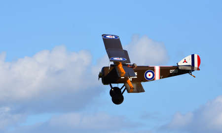 ICKWELL, BEDFORDSHIRE, ENGLAND - SEPTEMBER 06, 2020: Vintage  Sopwith Triplane  in flight blue sky and clouds.
